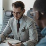 Homme qui mène un entretien de recrutement dans un bureau avec un candidat face à lui, assis